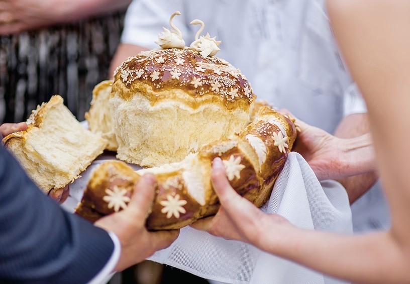 свадебный каравай, жених и невеста ломают каравай, традиция вручать каравай на свадьбе что значит, как ломают каравай на свадьбе.